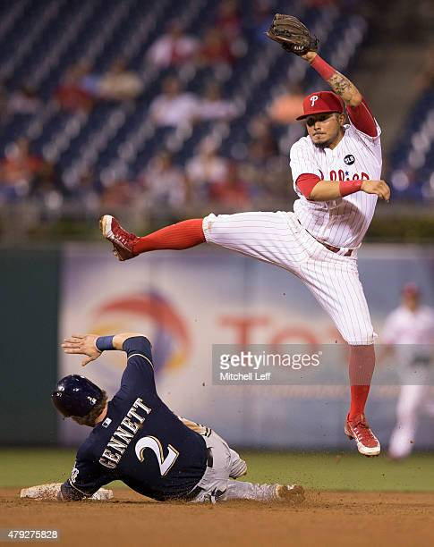 Freddy Galvis of the Philadelphia Phillies turns a double play as Scooter Gennett of the Milwaukee Brewers slide into him in the top of the tenth...