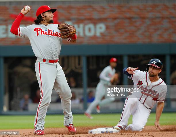 Freddy Galvis of the Philadelphia Phillies turns a double play over Ender Inciarte of the Atlanta Braves in the first inning at SunTrust Park on...
