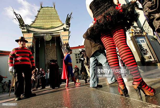 A Freddy Kruger fictional supernatural serial killer look–a–like left stands with other characters in front of Grauman's Chinese Theater in Hollywood...
