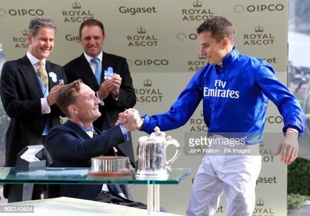 Freddy Tylicki presents the award to the winning Jockey William Buick after The Duke of Edinburgh Stakes during day four of Royal Ascot at Ascot...