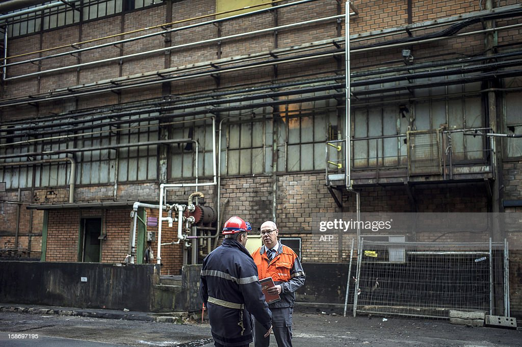 Frederic Midy (R), general director of Aperam stainless steel factory, controlled by the Mittal family, speaks with a firefighter on December 24, 2012 in Gueugnon, central France, after a fire broke out overnight, burning 4000 square meters with no casualties.