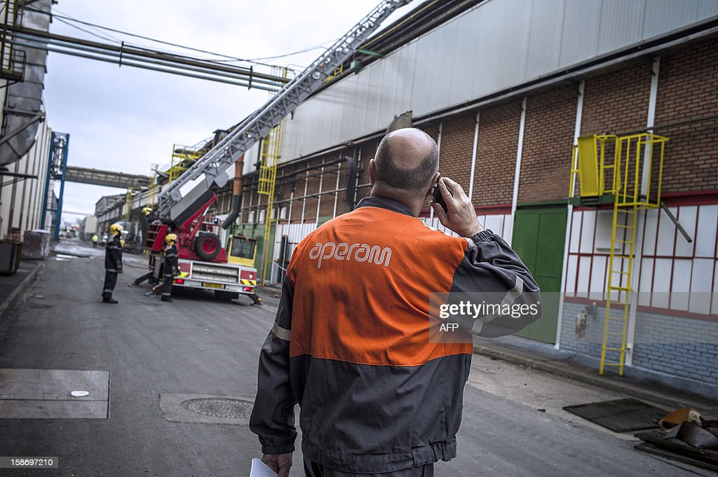 Frederic Midy, general director of Aperam stainless steel factory, controlled by the Mittal family, looks at firefighters while on the phone on December 24, 2012 in Gueugnon, central France, after a fire broke out overnight, burning 4000 square meters with no casualties. AFP PHOTO / JEFF PACHOUD