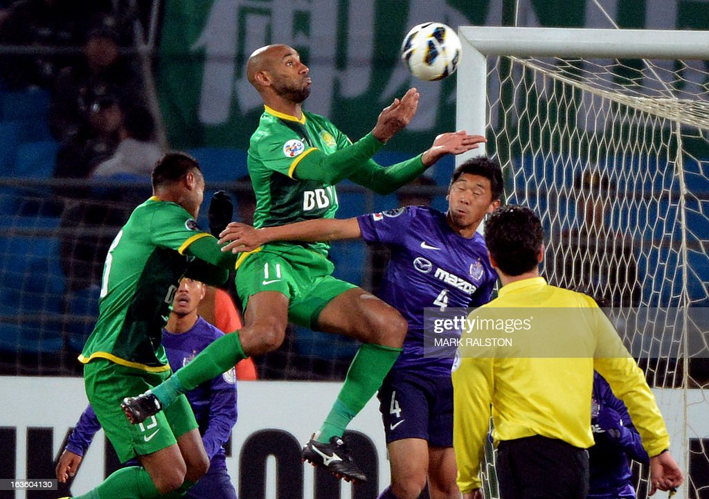 Frederic Oumar Kanoute (C) of Beijing Guo'an clashes with Mizumoto Hiroki of the Japanese team Sanfrecce Hiroshima during their AFC Champions League Group G football match at the Workers Stadium in Beijing on March 13, 2013. Guo'an went on to win 2-1. AFP PHOTO/ Mark RALSTON