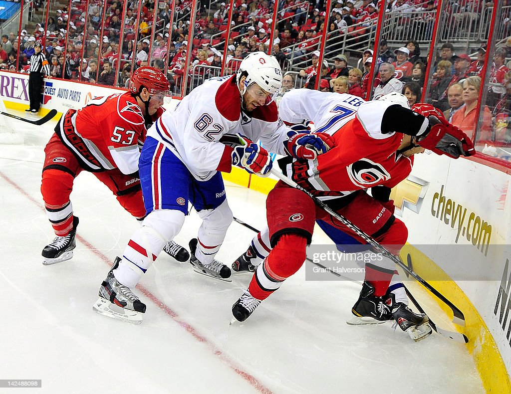 Frederic StDenis and Louis Leblanc of the Montreal Canadiens battle Jeff Skinner and Patrick Dwyer of the Carolina Hurricanes for a puck in the...