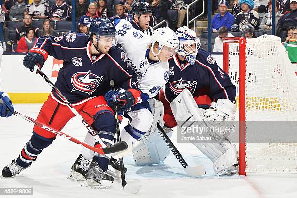Frederic StDenis of the Columbus Blue Jackets and Vladislav Namestnikov of the Tampa Bay Lightning battle for position while chasing down a loose...