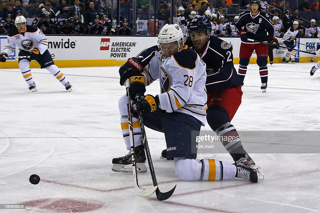 Frederic StDenis of the Columbus Blue Jackets knocks the puck away from Zemgus Girgensons of the Buffalo Sabres during the first period on September...