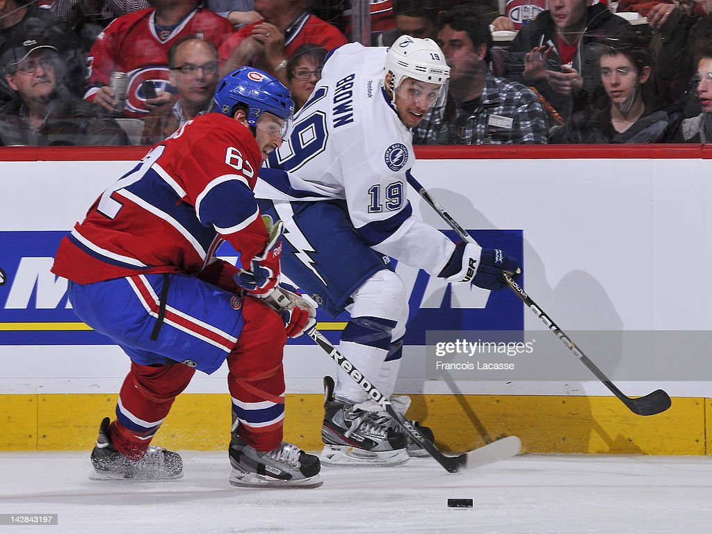 Frederic StDenis of the Montreal Canadiens and JT Brown of the Tampa Bay Lightning skate for the puck during the NHL game on April 4 2012 at the Bell...