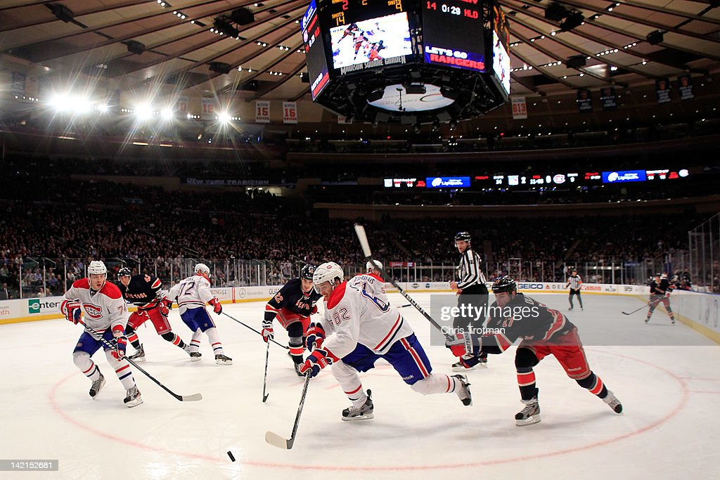 Frederic StDenis of the Montreal Canadiens controls the puck from Brandon Dubinsky of the New York Rangers at Madison Square Garden on March 30 2012...