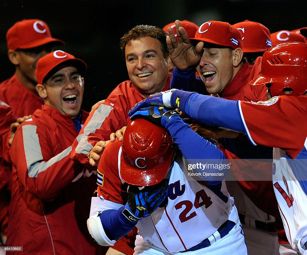 Frederich Cepeda #24 of Cuba is mobbed by his teammates and team doctor Antonio Castro, top center, son of former president of Cuba Fidel Castro, after hitting a three-run home run to end the game early on the mercy rule, 16-4, against Mexico during the 2009 World Baseball Celassic Pool B match on March 12, 2009 at the Estadio Foro Sol in Mexico City, Mexico.