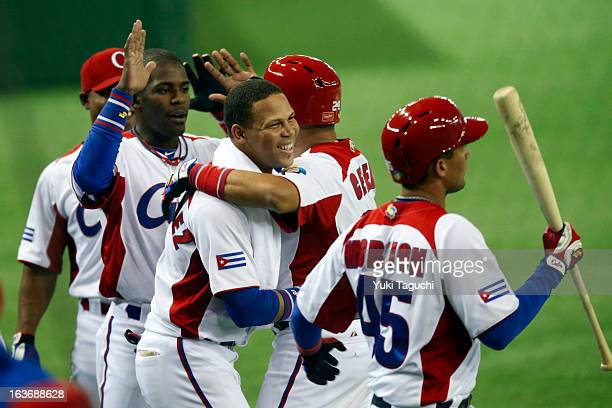 Frederich Cepeda of Team Cuba is greeted by teammates after scoring a run in the bottom of the fourth inning during Pool 1 Game 3 between the Chinese...