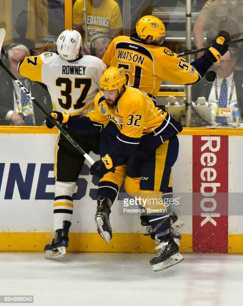 Frederick Gaudreau and Austin Watson of the Nashville Predators collide with Carter Rowney of the Pittsburgh Penguins during the first period in Game...