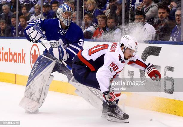 Frederik Andersen of the Toronto Maple Leafs comes out of his net to play the puck against Marcus Johansson of the Washington Capitals during the...
