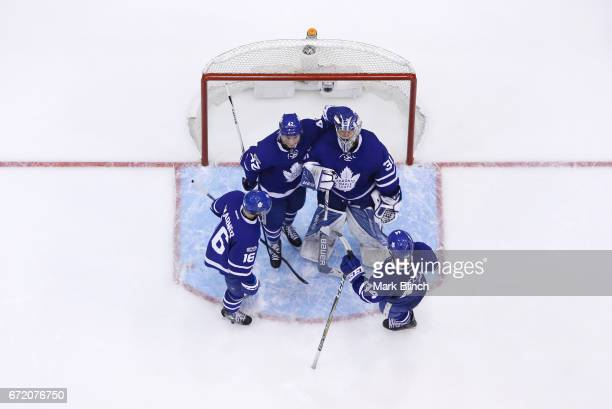 Frederik Andersen of the Toronto Maple Leafs is is consoled by teammates Tyler Bozak Mitch Marner and Morgan Rielly after the Leafs were defeated by...