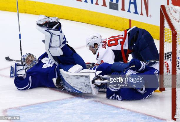 Frederik Andersen of the Toronto Maple Leafs is upended after being hit by Marcus Johansson of the Washington Capitals and Matt Hunwick of the...