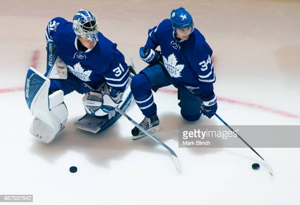 Frederik Andersen of the Toronto Maple Leafs kneels on the ice with teammate Auston Matthews during warmup at the Air Canada Centre before facing the...