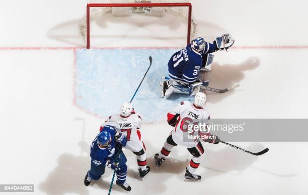 Frederik Andersen of the Toronto Maple Leafs makes a glove save alongside teammate Roman Polak against Chris Wideman and Mark Stone of the Ottawa...
