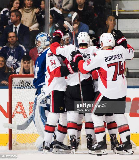Frederik Andersen of the Toronto Maple Leafs skates away as members of the Ottawa Senators celebrate a goal scored by Chris Wideman during the first...