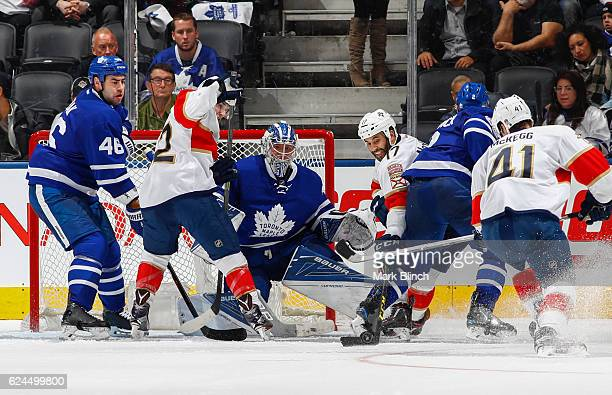 Frederik Andersen Roman Polak and Matt Hunwick of the Toronto Maple Leafs defend the net against Derek MacKenzie and Gregg McKegg the Florida...