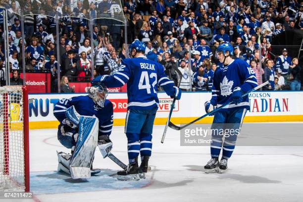 Frederik Andersen Tyler Bozak and Mitch Marner of the Toronto Maple Leafs react to losing the series against the Washington Capitals during overtime...