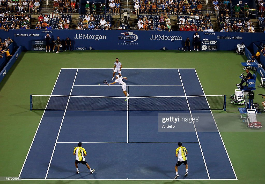 Frederik Nielsen of Denmark volleys in front of his partner Eric Butorac of the United States of America during their men's doubles second round...