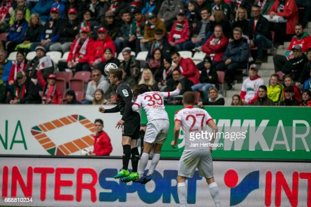Frederik Soerensen of Cologne and Takashi Usami of FC Augsburg in action during the Bundesliga match between FC Augsburg and 1 FC Koeln at WWK Arena...