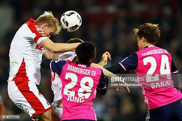 Frederik Sorensen of Koeln challenges for the headed ball with Gideon Jung and Gotoku Sakai of Hamburger SV during the Bundesliga match between 1 FC...