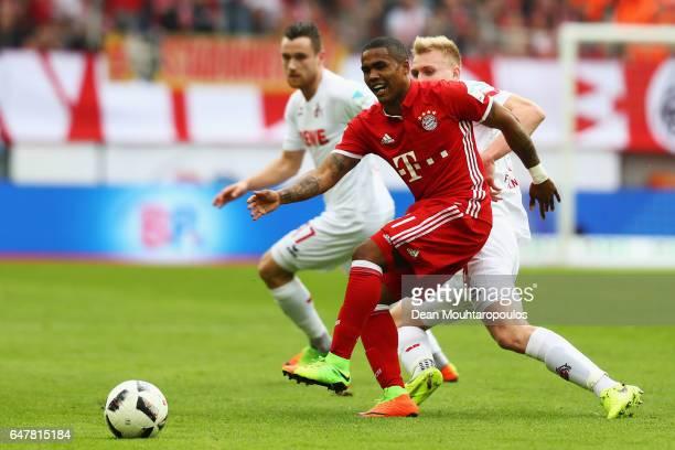 Frederik Sorensen of Koeln fouls Douglas Costa of Bayern Munich during the Bundesliga match between 1 FC Koeln and Bayern Muenchen at...