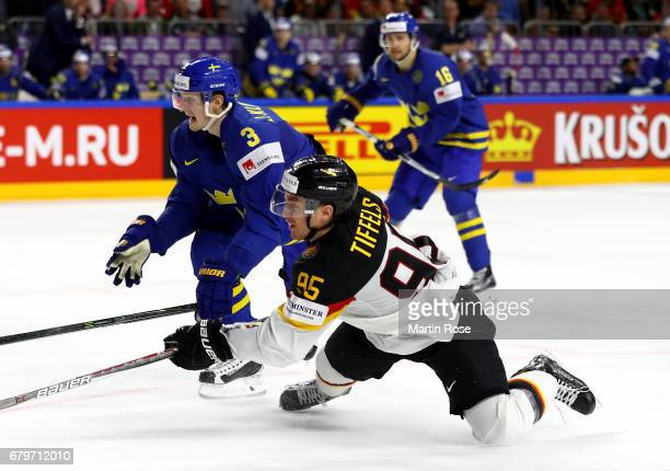 Frederik Tiffels of Germany challenges John Klingberg of Sweden for the puck during the 2017 IIHF Ice Hockey World Championship game between Germany...
