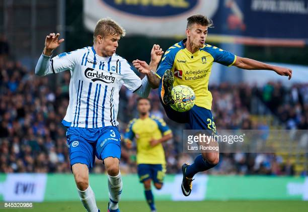 Frederik Tingager of OB Odense and Jan Kliment of Brondby IF compete for the ball during the Danish Alka Superliga match between OB Odense and...