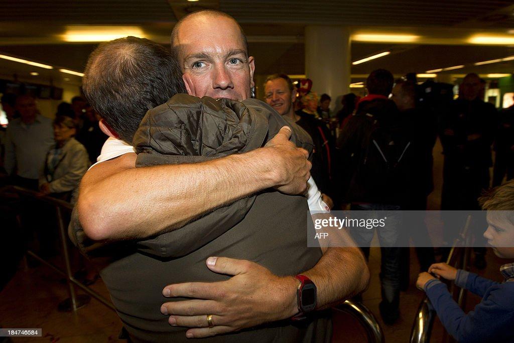 Frederik Van Lierde, winner of the Hawaii Ironman triathlon race embraces his coach Luc Van Lierde upon his arrival at Brussels Airport in Zaventem, on October 16, 2013.