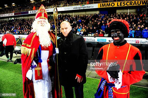 Frederik Vanderbiest poses with men dressed as Santa Claus and 'Zwarte Piet ' during the Jupiler League match between Club Brugge KV and KV Oostende...