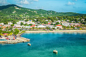 Beautiful scenery with harbor of St Croix, green mountain, water and town along the coastline.