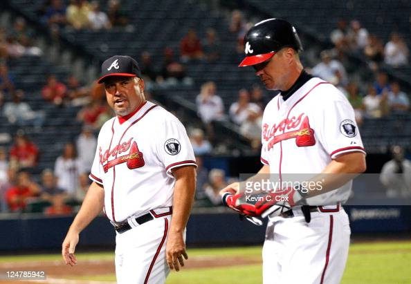 Fredi Gonzalez and Chipper Jones of the Atlanta Braves walk off the field after Jones beat out a ground ball in a collision at first base against...