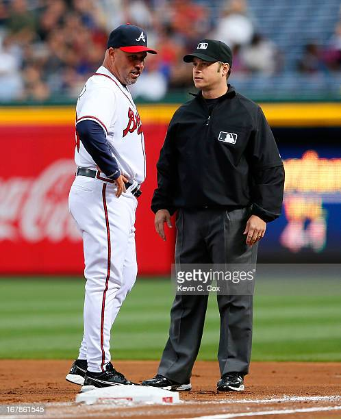 Fredi Gonzalez of the Atlanta Braves questions a call with first base umpire Mark Wegner in the first inning against the Washington Nationals at...