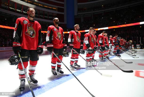 Fredrik Claesson Johnny Oduya Tom Pyatt JeanGabriel Pageau of the Ottawa Senators stand at attention during the singing of the national anthems prior...