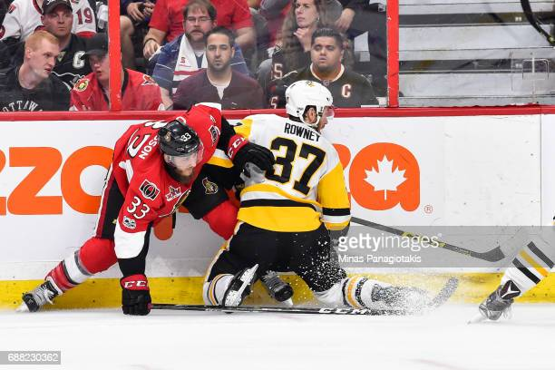 Fredrik Claesson of the Ottawa Senators and Carter Rowney of the Pittsburgh Penguins battle against the boards in Game Six of the Eastern Conference...