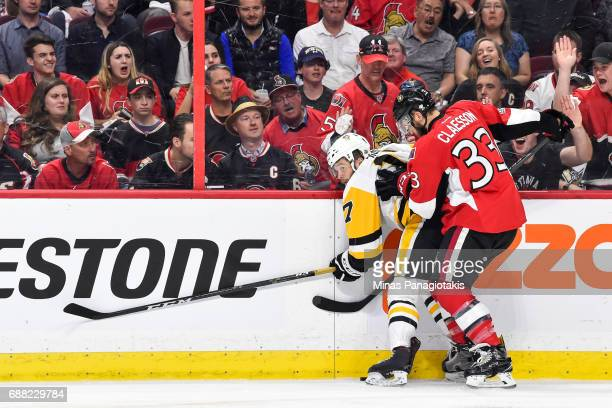 Fredrik Claesson of the Ottawa Senators pins Bryan Rust of the Pittsburgh Penguins against the boards in Game Six of the Eastern Conference Final...