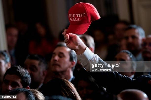Fredy Burgos of Virginia holds up a 'Build the Wall' hat while waiting with others for a Hispanic Heritage Month event in the East Room of the White...