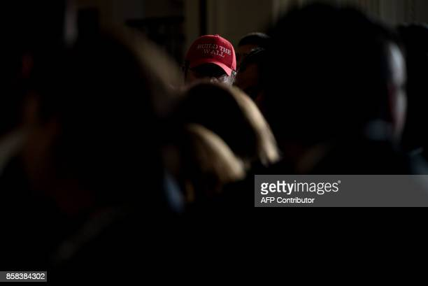 Fredy Burgos of Virginia wears a 'Build the Wall' hat while waiting with others for a Hispanic Heritage Month event in the East Room of the White...