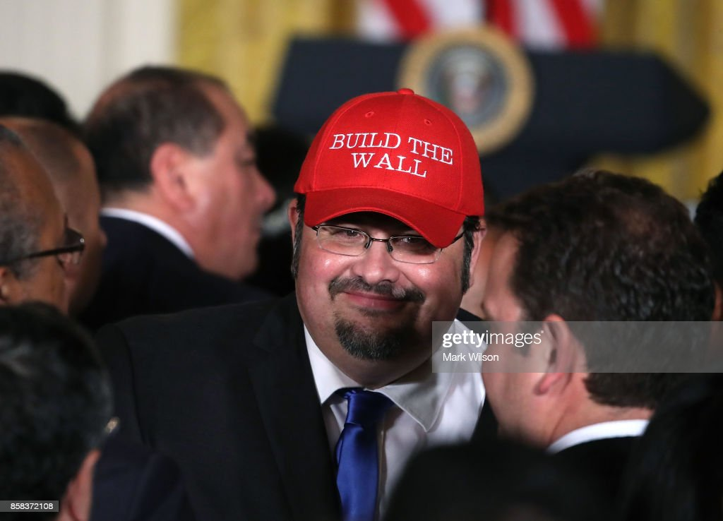 Fredy Burgos of Virginia wears a hat with the words 'Build The Wall' during an event to celebrate Hispanic Hertitage Month in the East Room at the White House, on October 6, 2017 in Washington, DC.