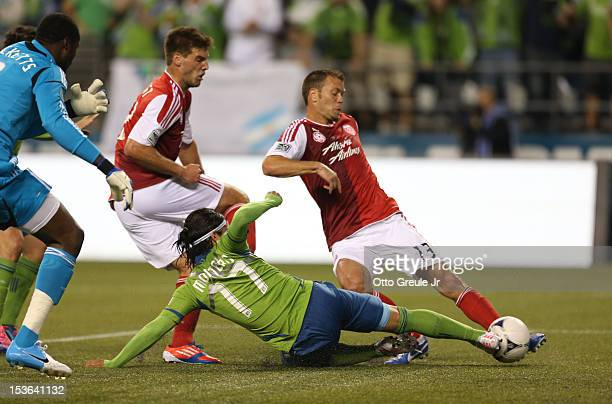 Fredy Montero of the Seattle Sounders FC scores a goal past Jack Jewsbury of the Portland Timbers at CenturyLink Field on October 7 2012 in Seattle...