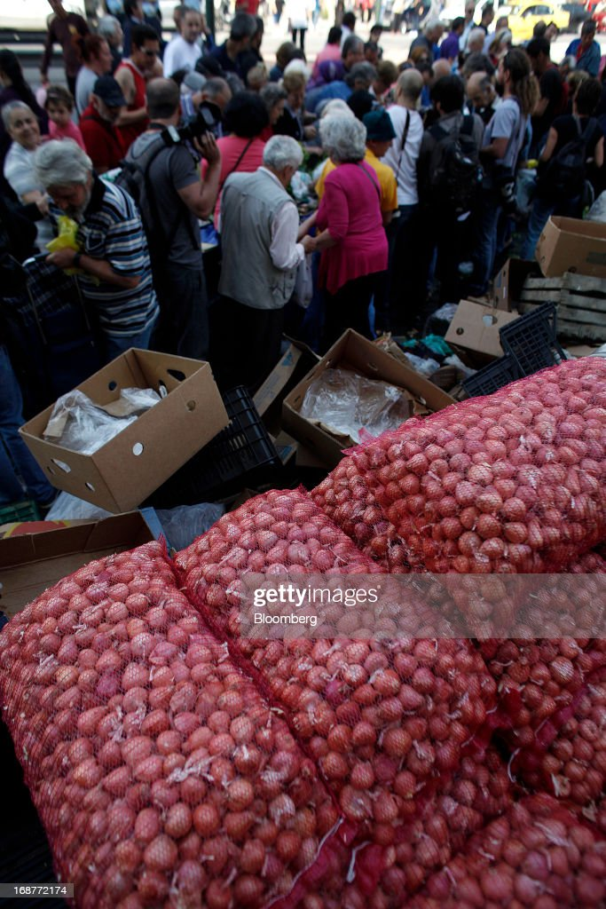 Free bags of onions sit stacked during a handout of leftover food by striking street vendors in Athens, Greece, on Wednesday, May 15, 2013. Greece's plans to return to international bond markets next year reflect the government's confidence it can draw a line under the country's debt crisis although the cost of borrowing suggests that might be premature. Photographer: Kostas Tsironis/Bloomberg via Getty Images