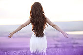 Free brunette woman with open arms enjoing sunset in lavender field. Harmony. Attractive girl with long curly hair style in white dress dreaming.