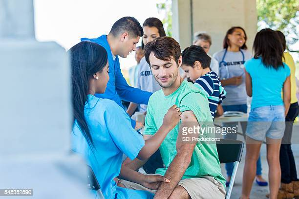 Free flu shot clinic with a handsome man recieving vaccination