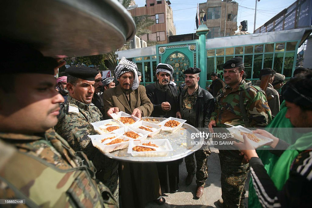 Free lunch is served to police and pilgrims taking part in the Arbaeen religious festival which marks the 40th day after Ashura commemorating the seventh century killing of Prophet Mohammed's grandson, Imam Hussein, in the shrine city of Karbala, southwest of Iraq's capital Baghdad, on January 1, 2013. AFP PHOTO/MOHAMMED SAWAF