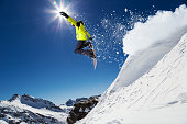 Free ride snowboarder jumping from hill