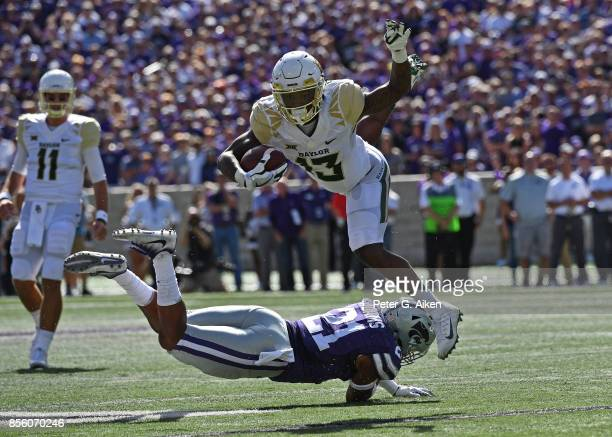Free safety Kendall Adams of the Kansas State Wildcats trips up wide receiver Tony Nicholson of the Baylor Bears during the first half on September...