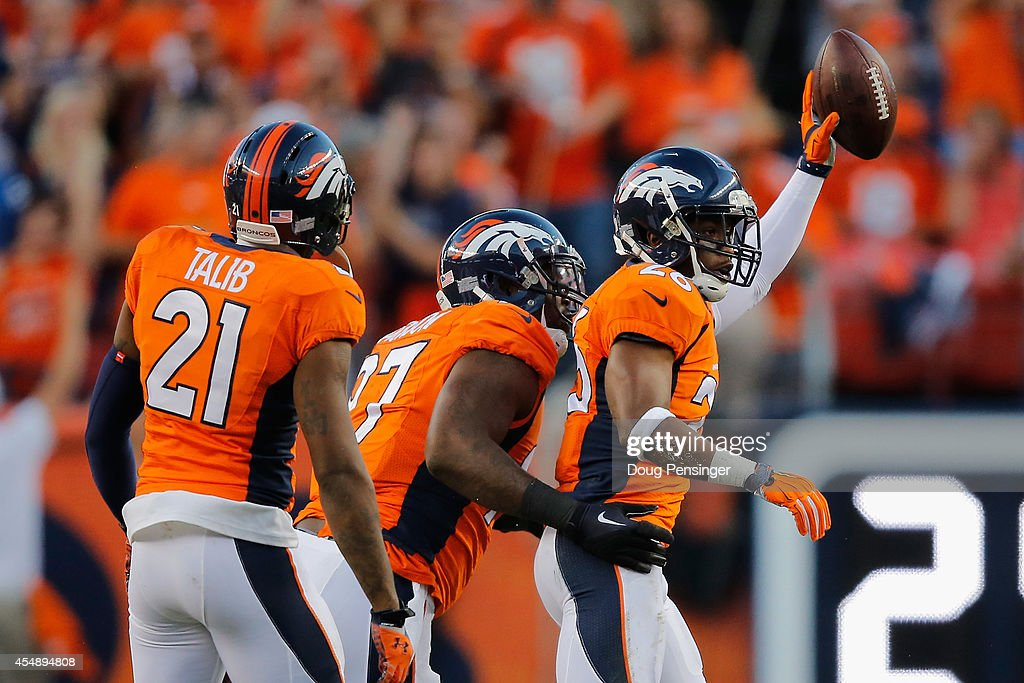 Free safety Rahim Moore #26 of the Denver Broncos celebrates his interception against the Indianapolis Colts with teammates cornerback Aqib Talib #21 and defensive end Malik Jackson #97 of the Denver Broncos at Sports Authority Field at Mile High on September 7, 2014 in Denver, Colorado.