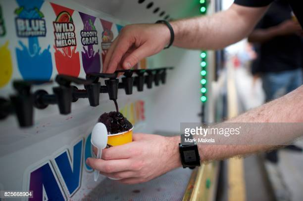 Free shaved iced is provided to job seekers waiting in line during an Amazon jobs fair at the Amazon Fulfillment Center on August 2 2017 in...