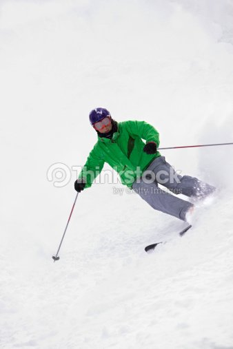 A free skier makes a turn, skiing down a hill.
